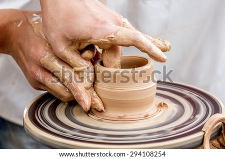 Close-up view of man working on pottery wheel and making clay pot - stock photo