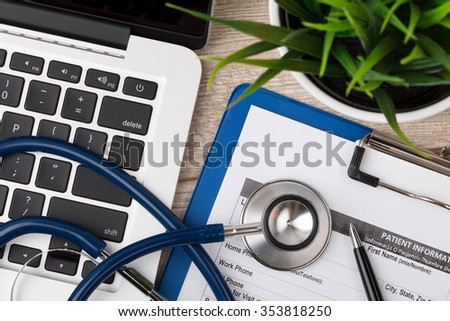 Close-up view of medical doctor working table. Laptop, stethoscope and patient information form. Healthcare and medical concept. - stock photo
