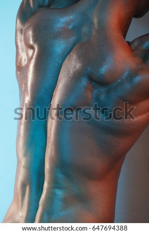 Close-up view of muscular male body in colored light. Studio shot