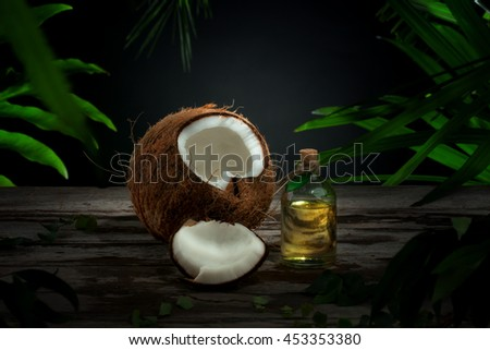 Close up view of nice fresh coconut and oil on green leaf background - stock photo