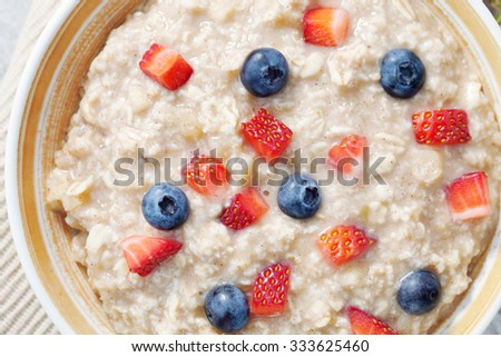 close up view of oatmeal porridge with strawberry and blueberry - stock photo