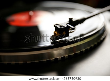 Close up view of old fashioned turntable playing a track from black vinyl. - stock photo