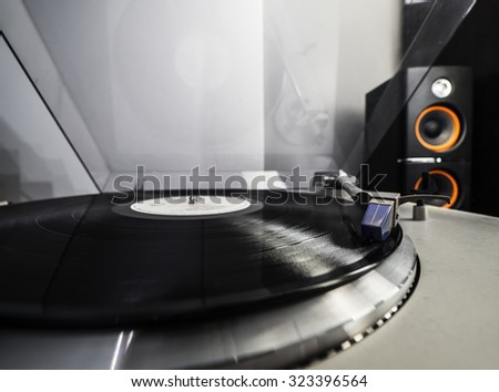 Close up view of old fashioned turntable playing a track from black vinyl - stock photo