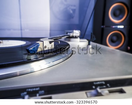 Close up view of old fashioned turntable playing a track from black vinyl with light bluish interior lightning - stock photo