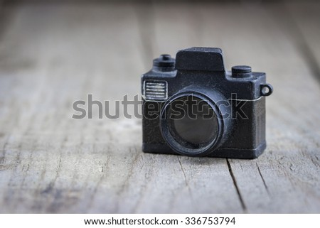 Close-up view of old small toy camera on wooden background - stock photo