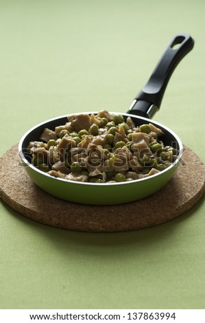 Close-up view of organic Seitan chops with green peas in a hot pan placed on a cork dish - stock photo