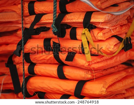 Close-up view of packed orange life-jackets pile ready for shipping. String with hook holding jacket. Safety control on board ship. Sea travelling. - stock photo