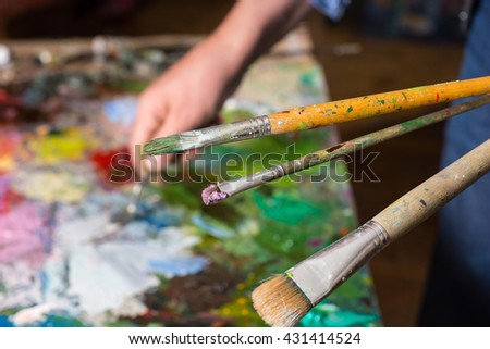Close up view of paintbrushes in one painter's hand under colorful palette in agallery - stock photo