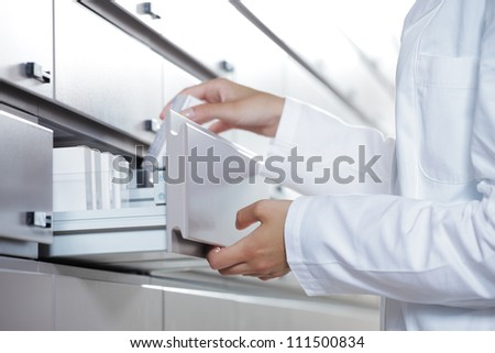 Close up view of pharmacist taking medicine from drawer - stock photo