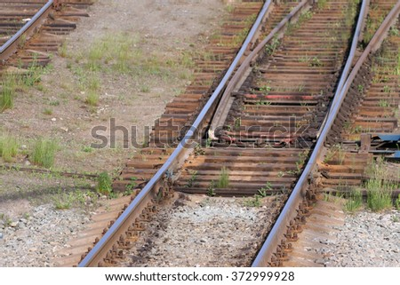 Close up view of railway with wooden sleepers, grass and turnout  - stock photo