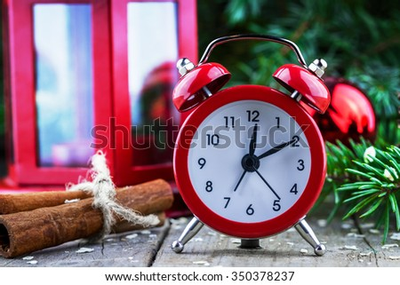 Close-up view of red alarm clock. New Year decoration composition