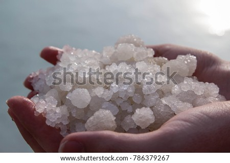 Close up view of round shape salt crystal formation (balls) in male hands shining in the sun against blue water background, Dead sea, Israel