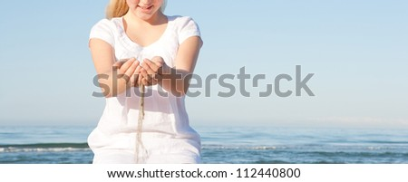 Close up view of sand filtering through a young girl's hands while sitting down on a beach with the sea in the background, smiling. - stock photo