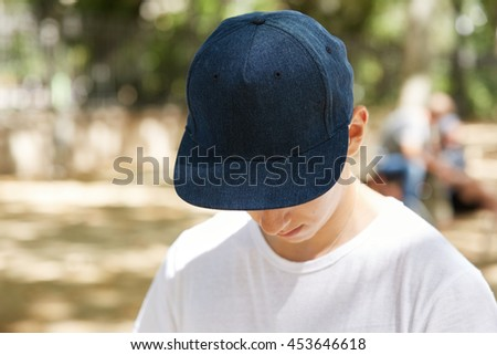 Close up view of schoolboy wearing dark blue blank snapback with copy space for your advertising content. Depressed teenager hiding his face under denim cap, looking down. Selective focus - stock photo