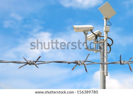 Close up view of security camera hanging among barbwire in prison or other guarded object with blue sky background. Modern ways of supervision. Using new technology in security and safety.  - stock photo