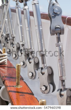 Close up view of several steel cables on a tall sail ship.
