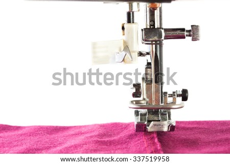 Close up view of sewing machine making stitch on fabric, isolated on white - stock photo
