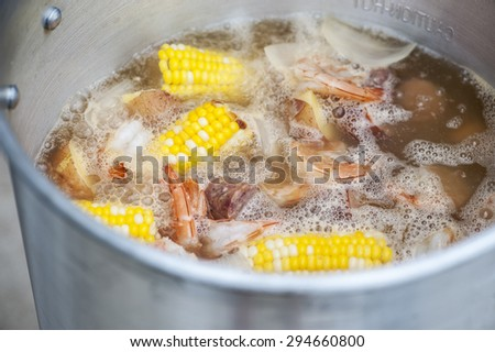 Close-up view of shrimp boil with corn, potatoes, shrimp, and sausage, shallow DOF - stock photo