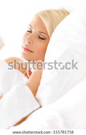 Close up view of sleepy woman in bed lying on the white cushion - stock photo