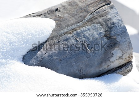 Close-up view of snow piled on icy, wooden log background, shallow DOF - stock photo