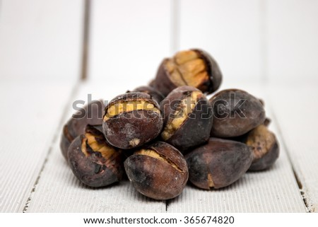Close up view of some delicious hot toasted chestnuts on white wooden background. - stock photo