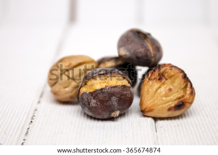 Close up view of some delicious hot toasted chestnuts on white wooden background.