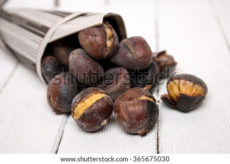 Close up view of some delicious hot toasted chestnuts wrapped on newspaper.
