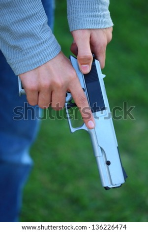 Close up view of someone cocking a gun or firearm - stock photo