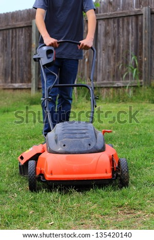 Close up view of someone mowing the lawn - stock photo