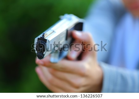 Close up view of someone pointing a gun at the camera