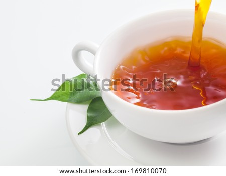 Close up view of someone pouring a cup of refreshing tea into a plain white cup with fresh green tea leaves resting on the saucer on a white background - stock photo