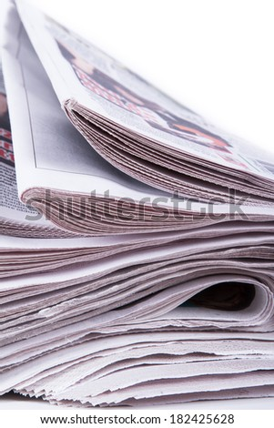 Close up view of stacked newspapers on white background.