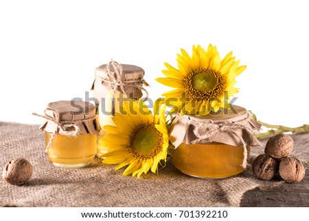 close-up view of sunflowers, nuts and fresh honey in glass jars on sackcloth