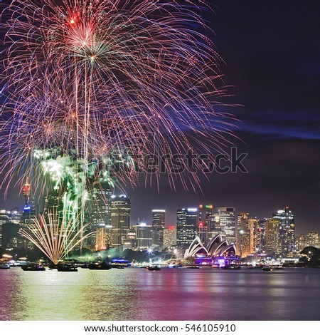 Close up view of Sydney New Year Eve Fireworks across Harbour above city CBD landmarks and towers.