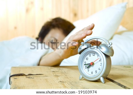 Close up view of  table clock and woman sleeping on back