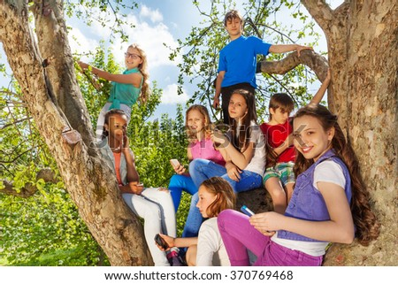 Close-up view of teens on the tree with mobiles - stock photo