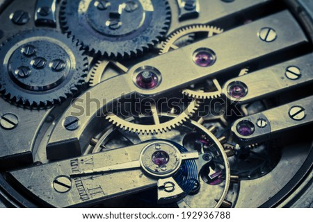 Close up view of the gears and mainspring in the mechanism of a silver pocket . Filtered image:cross processed vintage effect  - stock photo