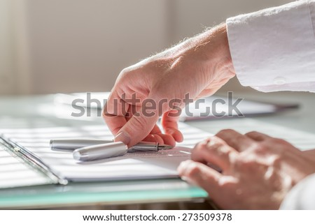 Close up view of the hand of a businessman reaching for his fountain pen lying on top of paperwork on his desk in the office. - stock photo