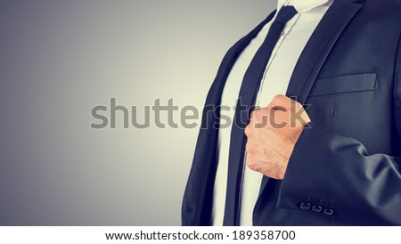 Close up view of the hand of a confident businessman in a suit standing at at angle holding the lapel of his jacket on a graduated grey background with copyspace. - stock photo