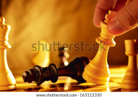 Close up view of the hand of a man going for checkmate in a game of chess using his king to knock over the opposing piece with dramatic sepia toned lighting and copyspace - stock photo