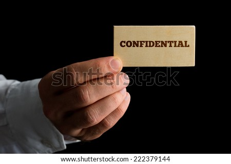 Close up view of the hand of a man holding a business card reading - Confidential - in a conceptual image over a black background with copyspace. - stock photo