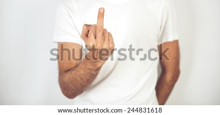 Close up view of the hand of a man making a rude obscene gesture with his middle finger in an insulting manner, close up of his torso and hand in a plain white t-shirt - stock photo