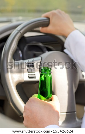 Close up view of the hand of a woman drinking while driving gripping a green bottle of spirits in one hand and steering with the other - stock photo