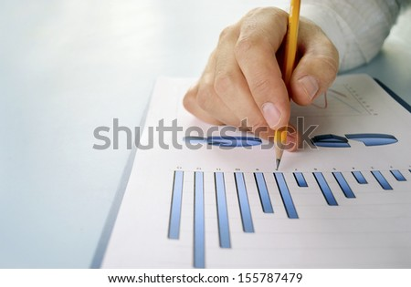 Close up view of the hand of a young business man in shirtsleeves holding a pencil working on a bar graph