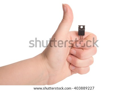 Close-up view of the hand of young girl gesturing with electronic components - transistor and microprocessor, taken on white background