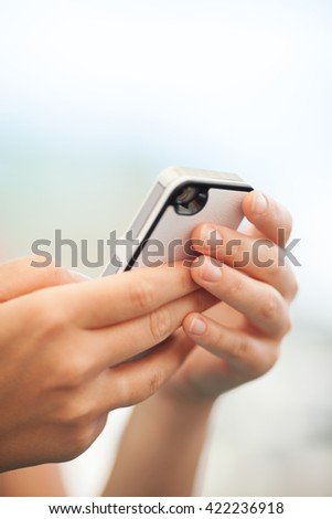 Close up view of the hands of a child checking a text message on a mobile or texting a friend - stock photo