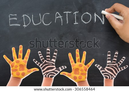 Close up view of the hands of a group of children gesture of approval an success with their hands raised against a blank chalkboard with copy space.hand painting children in school. back to school. - stock photo