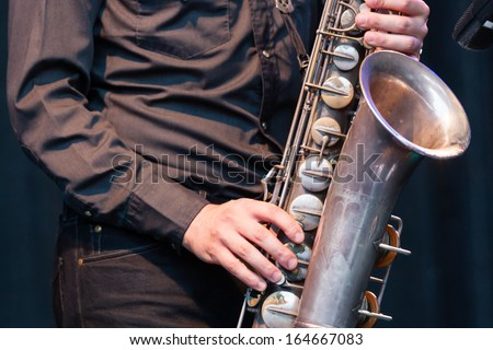 Close up view of the hands of a male saxophonist playing a tenor saxophone in an orchestra, a reed woodwind instrument popular in jazz, classical and blues music