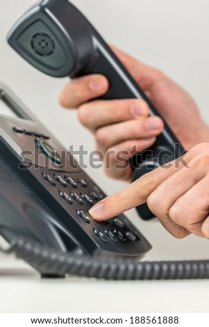 Close up view of the hands of a man dialing out on a landline telephone instrument using his finger to punch in the numbers on the keypad in a communications concept. - stock photo