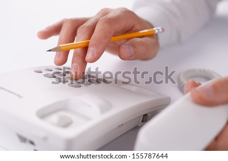 Close up view of the hands of a man making a telephone call on a landline holding the handset close to the camera and dialling in the number on the keypad with the other hand - stock photo
